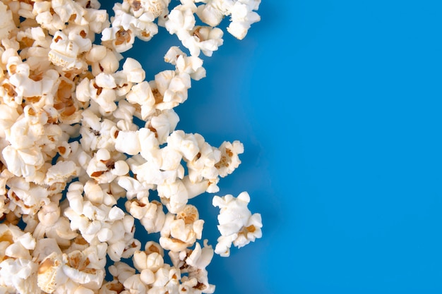 Primo piano di popcorn caldo fresco su fondo blu.