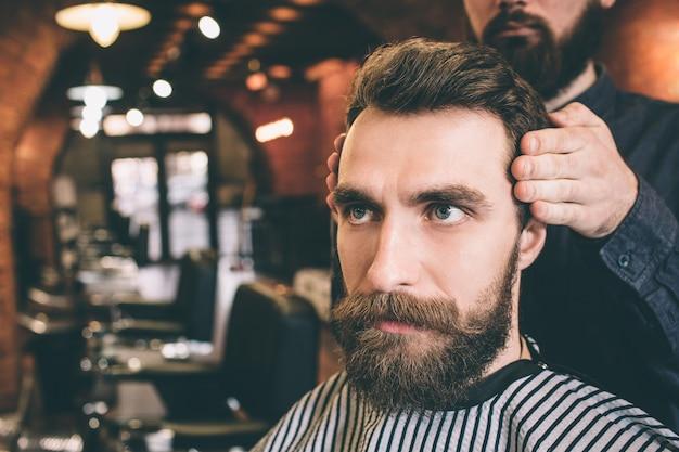 Primo piano di ragazzo serio e barbuto seduto in poltrona e guardando dritto in avanti. il suo parrucchiere si sta modellando i capelli.