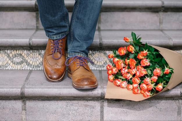 Primo piano di scarpe vintage con lacci viola e un mazzo di rose