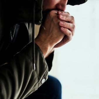 Primo piano di senzatetto seduta pensosa