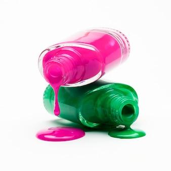 Primo piano di smalto rosa e verde che gocciola dalla bottiglia
