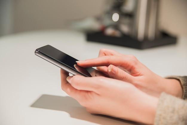 Primo piano di smartphone in mano. primo piano di una donna di mano che tiene uno smartphone e texting. mani di womans digitando su smartphone sopra tabella marrone di legno