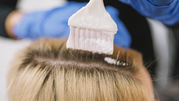 Primo piano di stilista che tinge i capelli del cliente