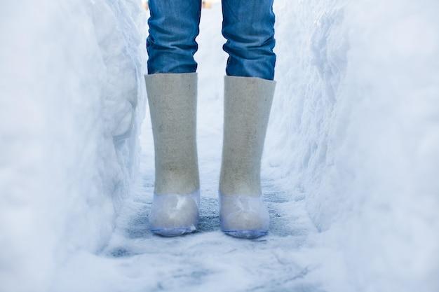 Primo piano di stivali caldi per i piedi degli uomini sulla neve bianca