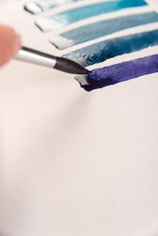 Primo piano di strisce blu sfumate su carta bianca