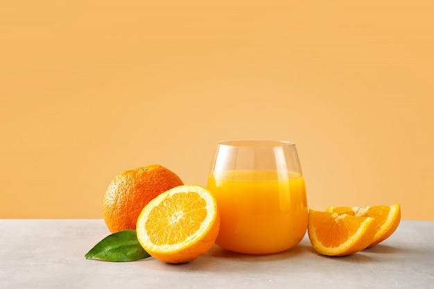 Primo piano di succo d'arancia in un bicchiere con arance su sfondo giallo alla moda