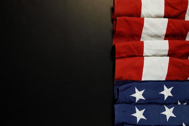 Primo piano di sventolando la bandiera americana nazionale usa su sfondo nero.