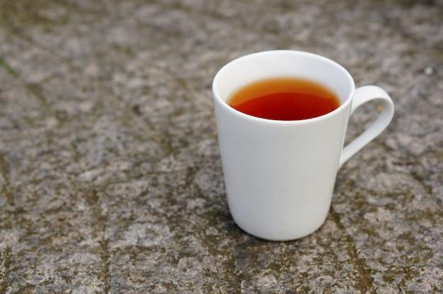 Primo piano di tè in una tazza bianca a terra sotto le luci con uno sfondo sfocato