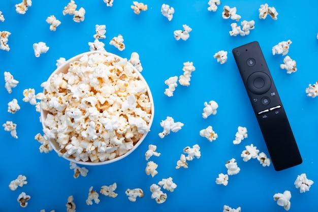 Primo piano di telecomando e popcorn caldo irascibile osservato da sopra su fondo blu