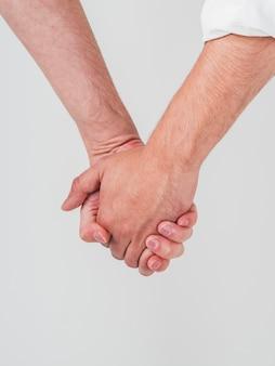 Primo piano di tenersi per mano delle coppie gay