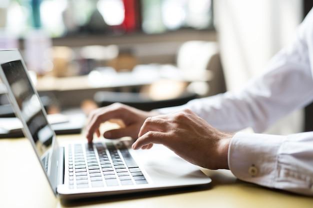 Primo piano di typing on keyboard dell'uomo d'affari