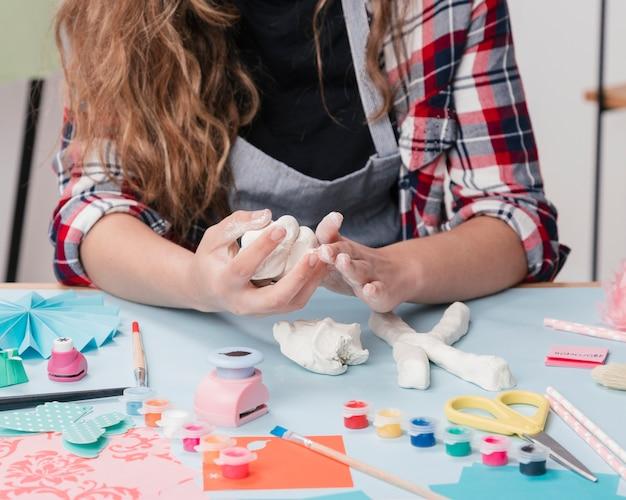 Primo piano di un artista femminile che fa lettera con argilla bianca