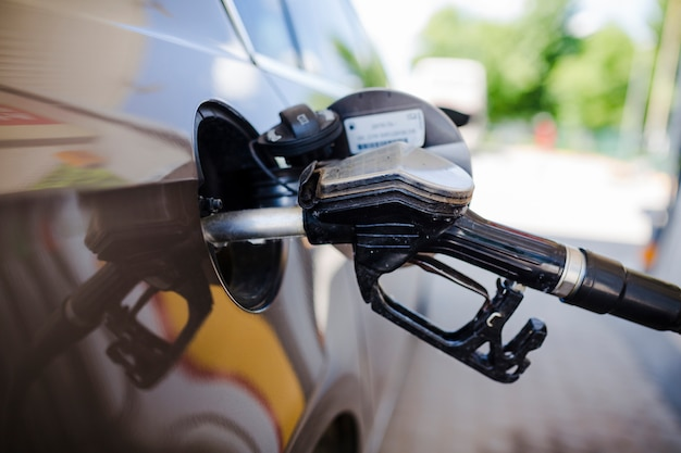 Primo piano di un'automobile che rifornisce di carburante alla stazione di servizio