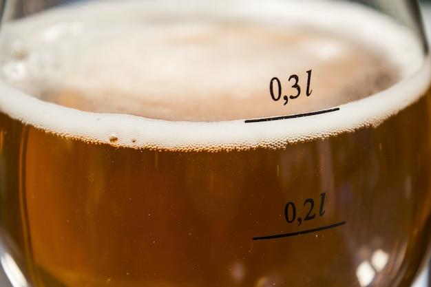 Primo piano di un bicchiere di birra fredda sotto la luce del sole
