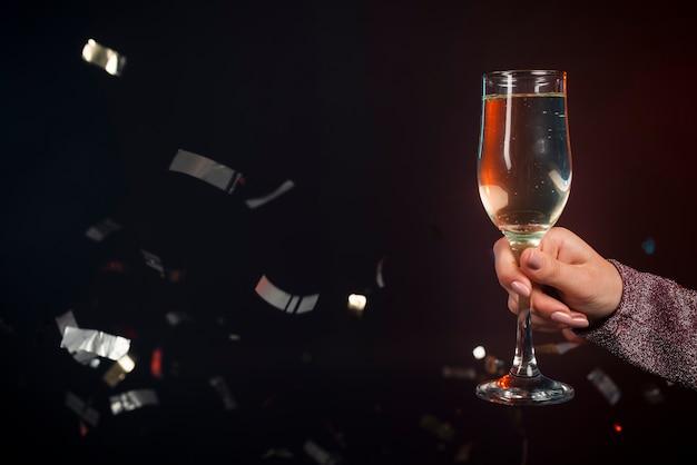 Primo piano di un bicchiere di champagne con coriandoli