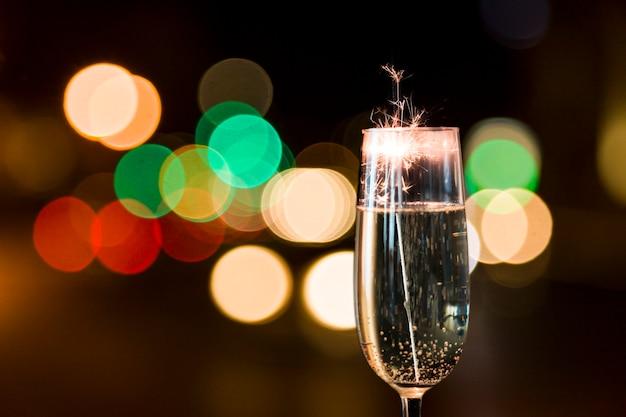 Primo piano di un bicchiere di champagne con fuochi d'artificio