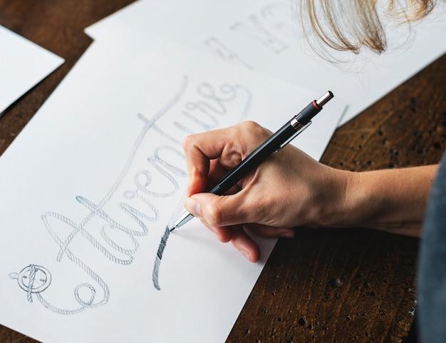 Primo piano di un calligrafo che lavora ad un progetto