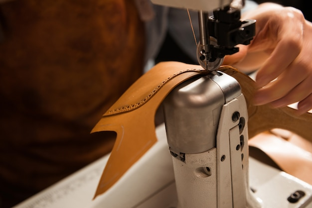 Primo piano di un calzolaio che cuce una parte della scarpa