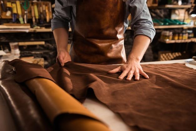 Primo piano di un calzolaio che lavora con tessuto in pelle
