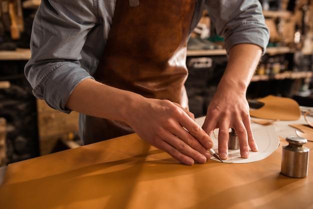 Primo piano di un calzolaio taglio di cuoio