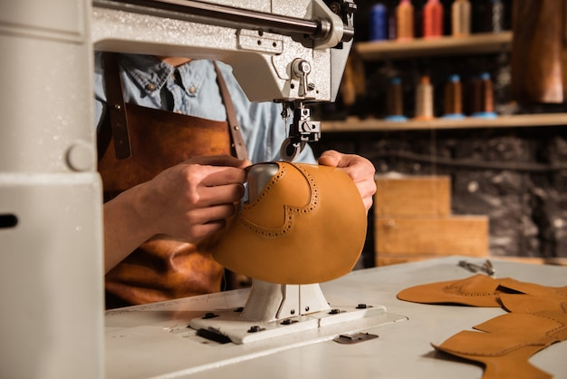 Primo piano di un calzolaio utilizzando la macchina da cucire