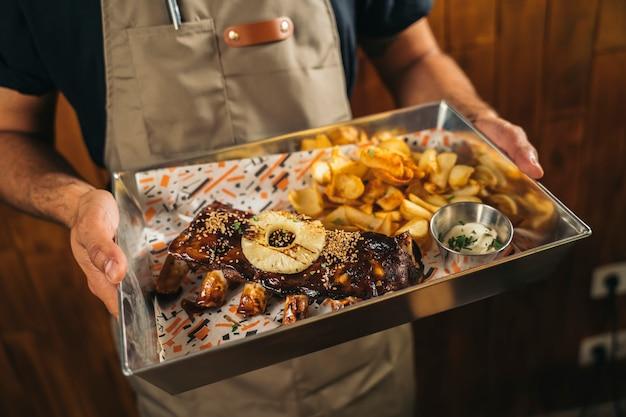Primo piano di un cameriere che serve costolette alla brace deliziose con patatine fritte