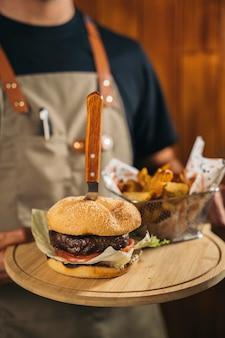 Primo piano di un cameriere che serve un delizioso hamburger di carne con patatine fritte