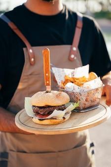 Primo piano di un cameriere che serve un delizioso hamburger, patatine fritte e salsa servita su assi di legno.