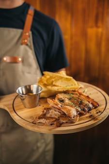 Primo piano di un cameriere che serve un delizioso piatto di carne con patatine fritte
