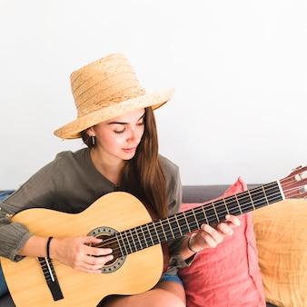 Primo piano di un cappello da portare dell'adolescente che gioca chitarra