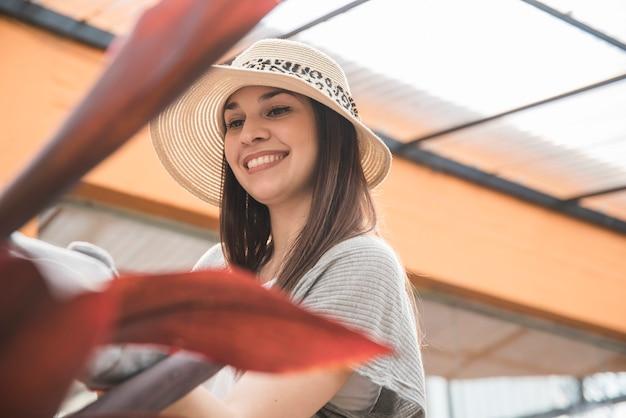 Primo piano di un cappello da portare felice della giovane donna in serra