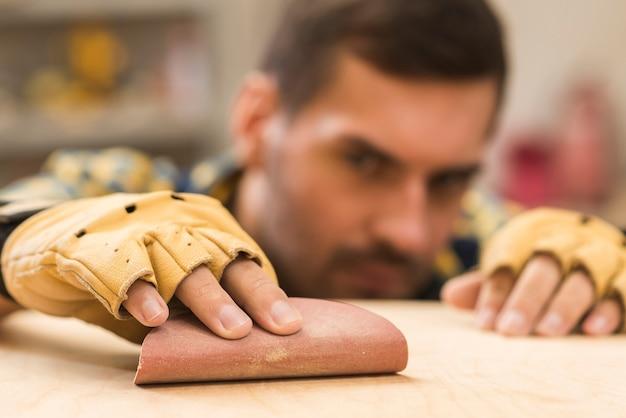 Primo piano di un carpentiere maschio che indossa la carta vetrata sfregante dei guanti protettivi in mano sulla plancia di legno