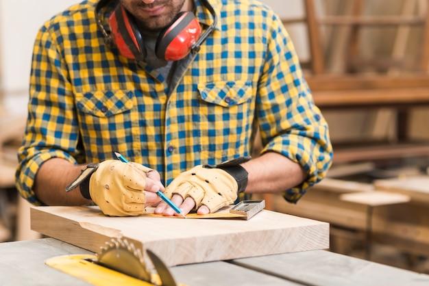 Primo piano di un carpentiere maschio che lavora nell'officina