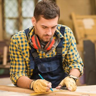 Primo piano di un carpentiere maschio che misura la plancia di legno lunga con il righello