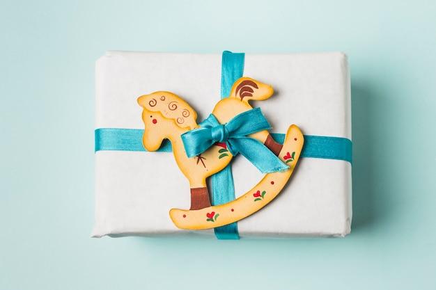 Primo piano di un contenitore di regalo e del giocattolo del cavallo a dondolo legati con il nastro blu su fondo
