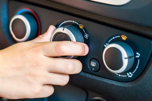 Primo piano di un controllo di temperatura girante dell'automobile della mano umana, colpo basso di profondità di campo