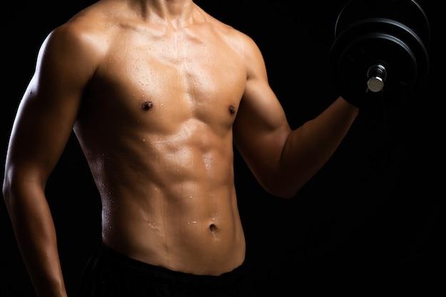 Primo piano di un corpo di forza fitness con manubri. giovane in forma