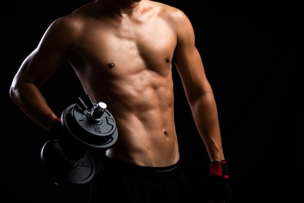 Primo piano di un corpo di forza fitness con manubri.