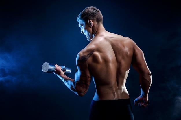 Primo piano di un culturista atletico bello dell'uomo di potere che fa gli esercizi con la testa di legno. corpo muscoloso fitness su sfondo scuro fumo. maschio perfetto. culturista fantastico, tatuaggio, posa.