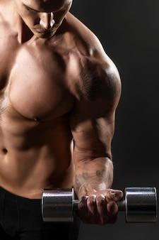 Primo piano di un culturista atletico bello dell'uomo di potere che fa gli esercizi con la testa di legno. corpo muscoloso fitness su sfondo scuro. messa a fuoco selettiva. culturista fantastico, tatuaggio, posa.