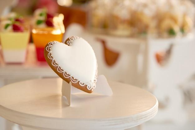 Primo piano di un delizioso biscotto smaltato a forma di cuore in piedi sul supporto di legno vicino al candybar con diversi dessert come cupcakes gialli e gelatine rosse.