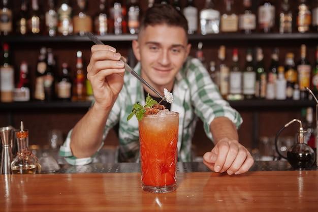 Primo piano di un delizioso coktail con ghiaccio, barista professionista sta decorando. barman lavora nel suo ristorante e prepara un drink per il cliente