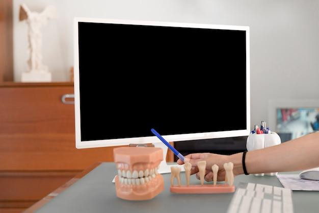 Primo piano di un dentista che punta sullo schermo del computer vuoto in clinica
