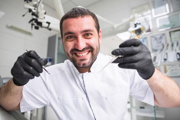 Primo piano di un dentista maschio felice che tiene gli strumenti dentali
