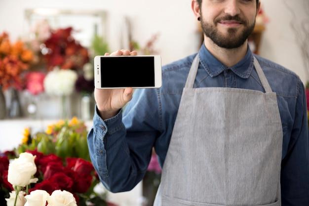 Primo piano di un fiorista maschio che mostra l'esposizione del cellulare nel suo negozio di fiore