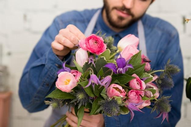 Primo piano di un fiorista maschio che organizza i fiori nel mazzo