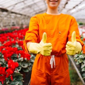 Primo piano di un giardiniere che gesturing i pollici su