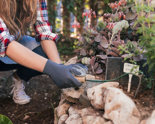 Primo piano di un giardiniere femminile che scava il terreno con la zappa di mano nel giardino
