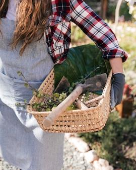Primo piano di un giardiniere femminile che tiene zappa e ramoscelli raccolti nel cestino