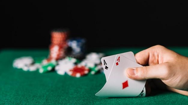Primo piano di un giocatore che tiene una carta di due assi sul tavolo da poker